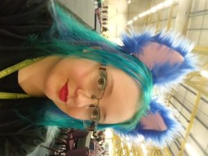 Dragon is looking into the camera with her face turned partially to the side. She wearing black clothes with a lanyard and red lipstick. Turquoise and mid blue hair is topped with royal blue fluffy ears. In the background is a convention hall