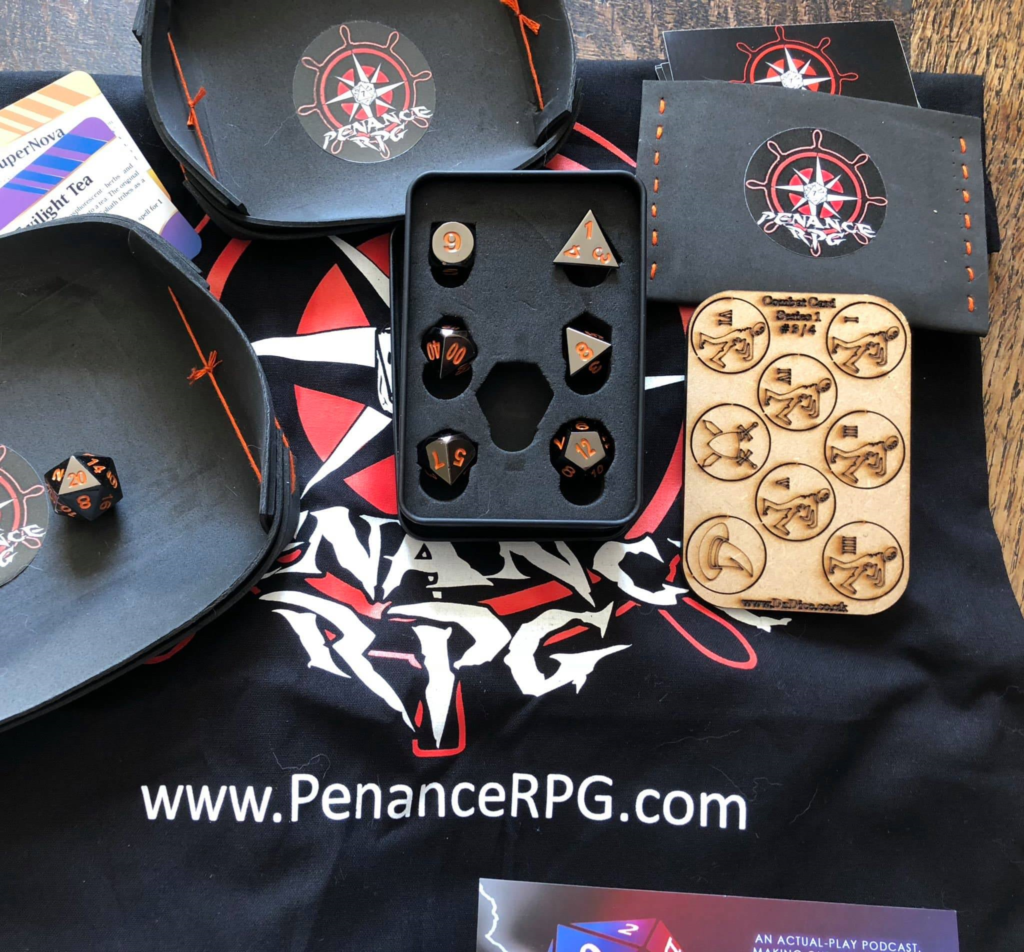 Penance RPG prize, mainly black items with red logos or orange detailing to match the shiny black metal dice with orange numbers. Includes a bag and two dice trays