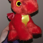 A hand in black and purple sleeves holding a red dragon with a yelloww shiny chest, yellow eyes and shiny red wings