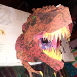 An open book with illustrations of dinosaur skull and a pop-up tyrannosaurus